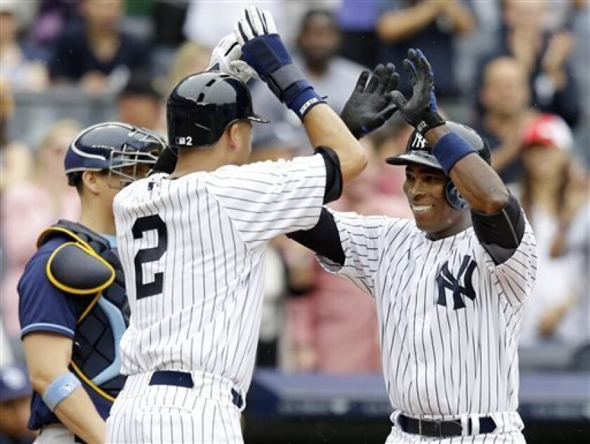 New York Yankees Derek Jeter (2) greets Alfonso Soriano at the plate after scoring on Soriano's third-inning, two-run home run in the MLB American League baseball game, Sunday, July 28, 2013, in New York. (AP Photo/Kathy Willens)