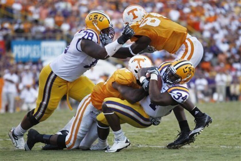 LSU running back Stevan Ridley (34) is tackled on a rushing play during the second half of an NCAA football game against Tennessee in Baton Rouge, Saturday, Oct. 2, 2010. (AP Photo/Gerald Herbert)