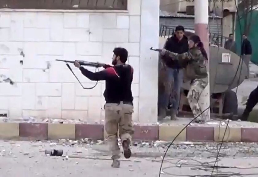 FILE - In this March 18, 2013, file image taken from video obtained from the Shaam News Network, which has been authenticated based on its contents and other AP reporting, free Syrian Army fighters fire at Syrian army soldiers during a fierce firefight in Daraa al-Balad, Syria. Syrian rebels backed