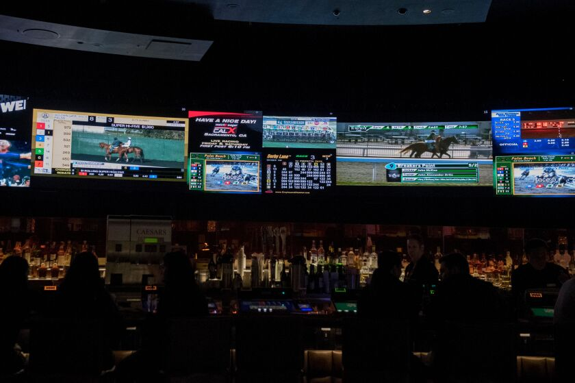 Horse racing is on display at a sports book at Caesars Palace Hotel and Casino in Las Vegas on March 13, 2020.