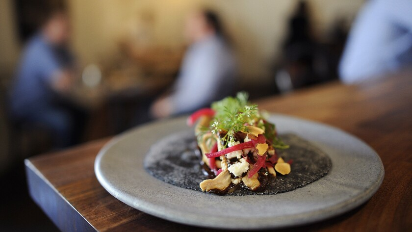 A chicken mole taco made with almonds, queso fresco and dates, garnished with cilantro at Taco Maria in Costa Mesa.
