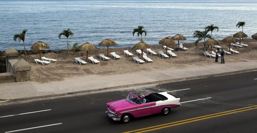 """A car passes in front of an installation titled """"Resaca"""" by Cuban artist Arles del Rio, part of the 12th Havana Biennial in Cuba. The artist transformed a patch of boardwalk into a beach."""