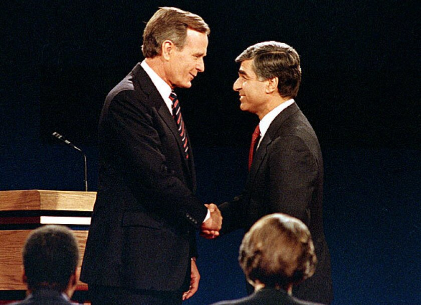 George H.W. Bush, left, and Michael Dukakis shake hands before a debate prior to the 1988 election.