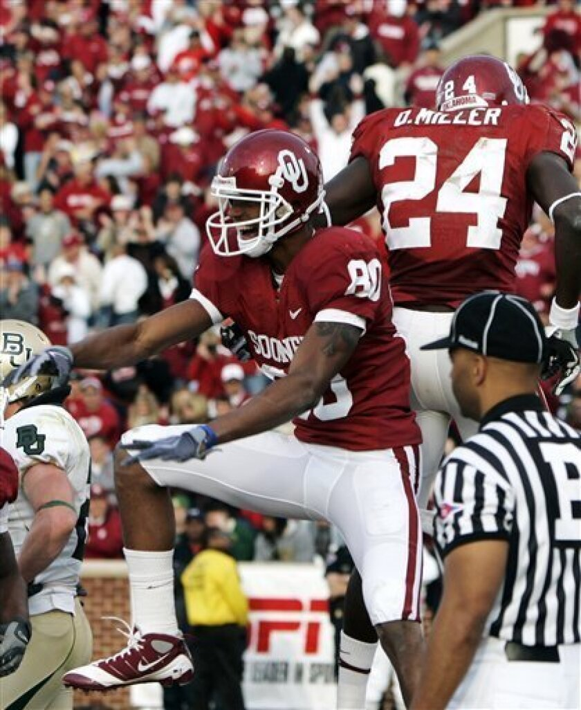 Oklahoma's Adron Tennell (80) celebrates with teammate Dejuan Miller (24) after making a touchdown in the fourth quarter of an NCAA college football game against Baylor in Norman, Okla., Saturday, Oct. 10, 2009. Oklahoma won the game 33-7. (AP Photo/Sue Ogrocki)