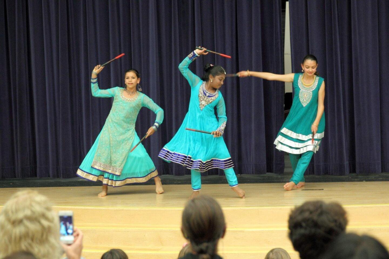 Vishaala Wilkinson, Naomika Raveendran, and Sheila Menon perform an Indian stick dance