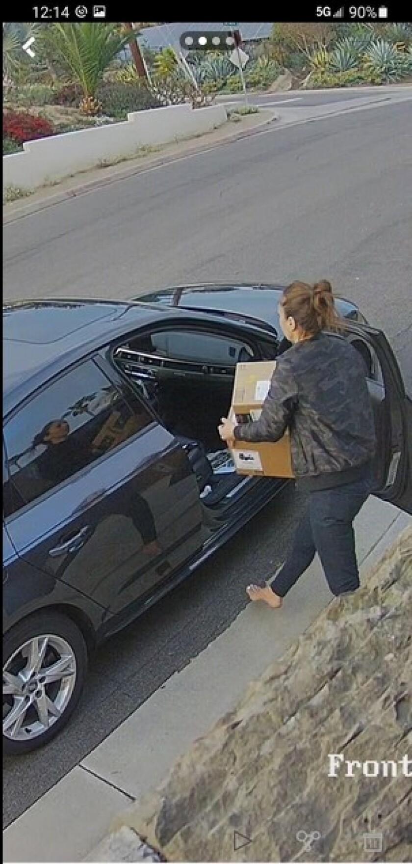 A woman suspected of stealing packages from a La Jolla porch is seen on home security footage putting them in a waiting car.
