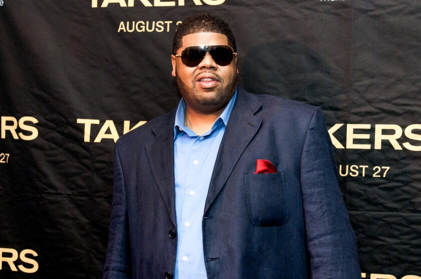 A man in a sport coat and wearing sunglasses