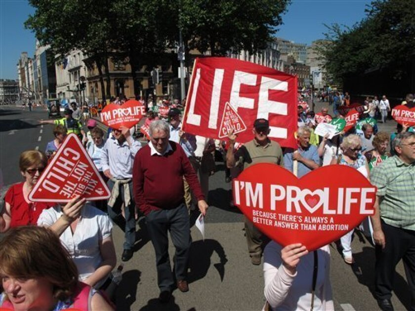 Anti-abortion protesters holding placards walk through Ireland's capital, Dublin, in an anti-abortion protest Saturday, July 6, 2013. More than 35,000 activists marched to the parliament building to oppose Irish government plans to enact a bill legalizing terminations for women in life-threatening pregnancies. The Protection of Life During Pregnancy Bill is expected to be passed into law next week. (AP Photo/Shawn Pogatchnik)