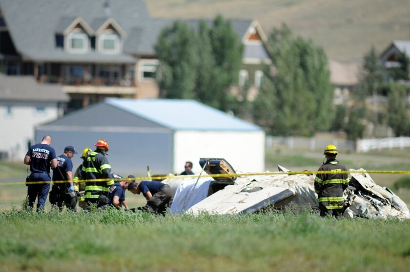 Police and firefighters work on the scene where three people were killed and two others injured after an airplane crashed in a field northwest of the main runway at Erie Municipal Airport while coming in for a landing in Erie, Colo., Sunday, Aug. 31, 2014. (AP Photo/The Daily Camera, Cliff Grassmick)