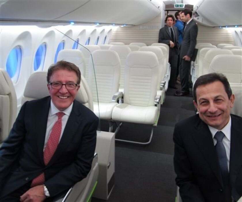 Bob Deluce, left, president and CEO of Porter Airlines, sits with Bombardier president Mike Arcamone inside a Bombardier CS100 model after Deluce announced the airline's conditional purchase of 12 of the planes on Wednesday, April 10, 2013. Porter Airlines is seeking permission to land jets at Toronto's island airport and extend the runway on the city's waterfront as the upstart airline seeks to expand to destinations across North America. (AP Photo/Rob Gillies)