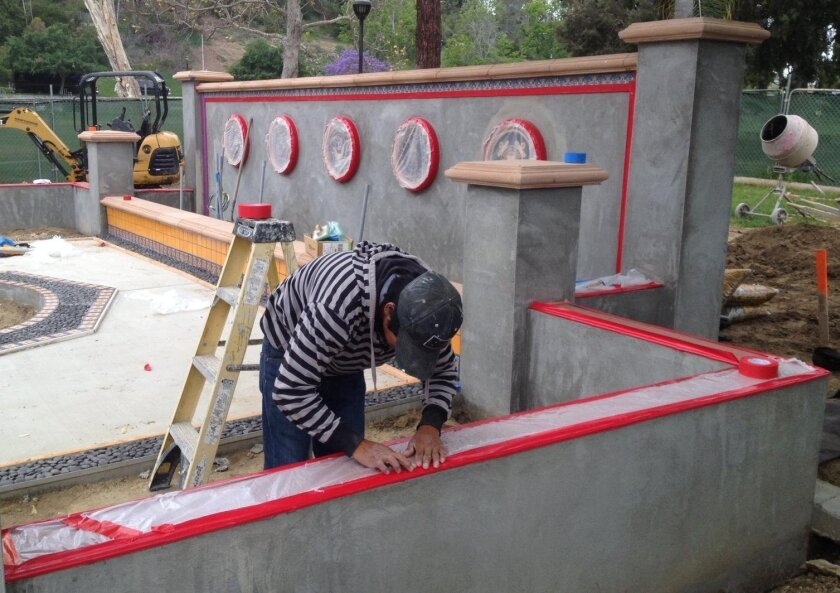 Victor Ramirez works on a wall at the veterans honor courtyard being finished at La Colonia Park in Solana Beach.