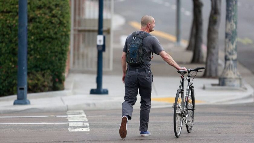 A commuter walks his bicycle across the street along Park Avenue.