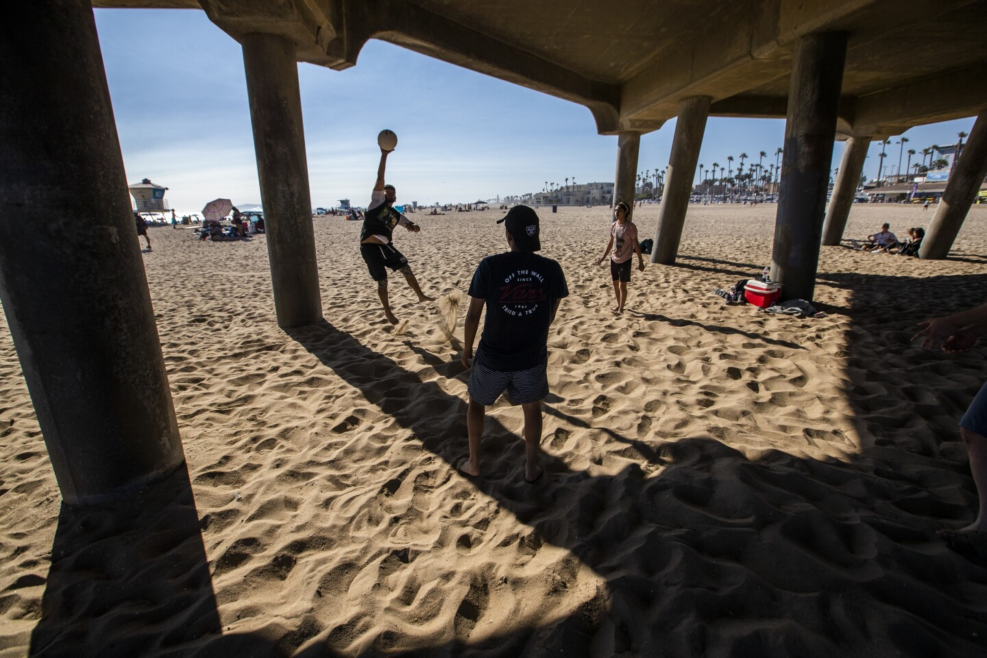 HUNTINGTON BEACH, CA - JUNE 10: Jorge Tafolla, of Los Angeles, hits a volleyball around with friends in the shade of the pier to cool off amid high temperatures Wednesday, June 10, 2020 in Huntington Beach, CA. A heat advisory will be in effect today from 11 in the morning until 7 tonight throughout Southern California. (Allen J. Schaben / Los Angeles Times)