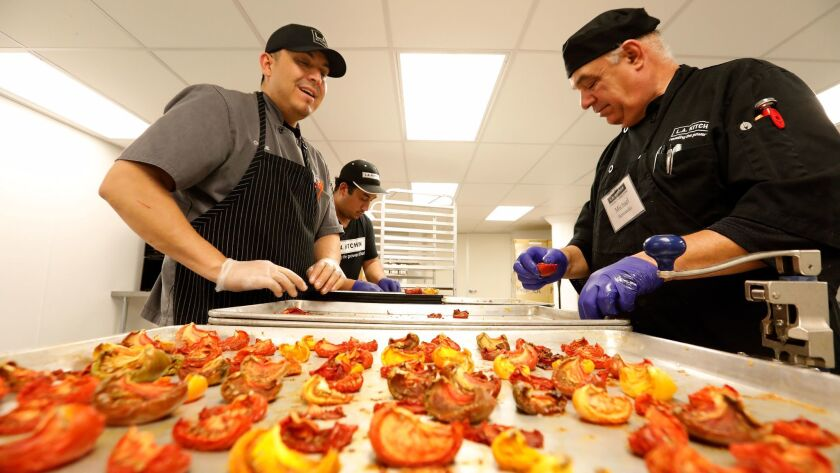 Charlie Negrete, left, works with students Jose Moreno, center, and Michael Hernandez as they prepare to turn oven dried tomatoes into tomato powder.