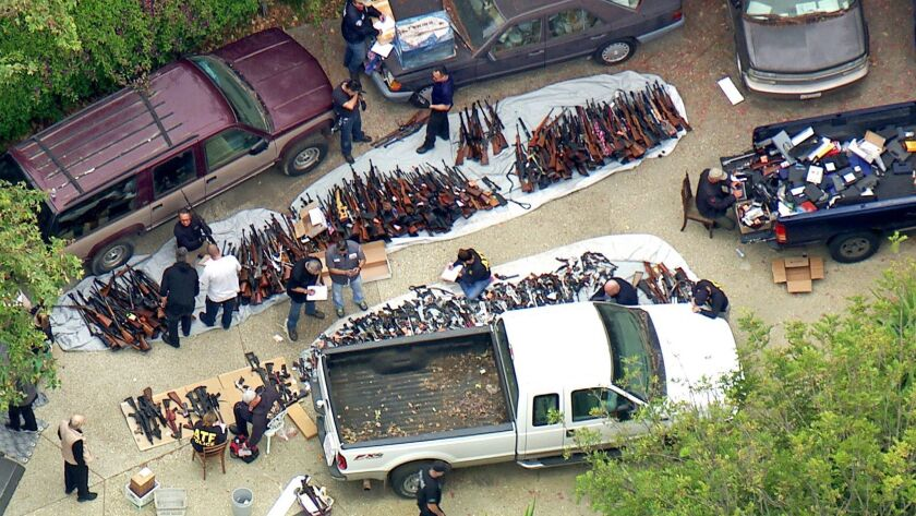 This photo from a video provided by KCBS/KCAL-TV shows investigators from the U.S. Bureau of Alcohol, Tobacco, Firearms and Explosives and the LAPD inspecting a large cache of weapons seized at a Bel-Air home on Wednesday,