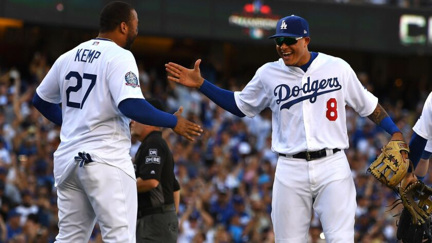 Matt Kemp, left, and Manny Machado celebrate after the Dodgers defeated the Colorado Rockies to clinch their sixth straight division championship on Oct. 1.