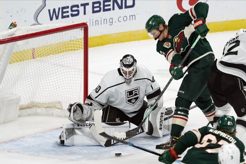 Minnesota Wild's Nick Bjugstad attempts to make a shot as Kings' goalie Calvin Petersen stops the attempt.
