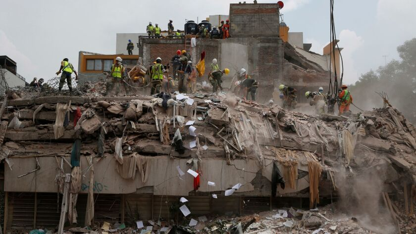 Workers shovel papers and debris off the top of the rubble of a building that collapsed in last week's Mexico earthquake, in the Del Valle neighborhood of Mexico City.