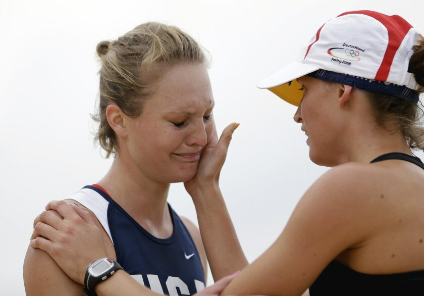 FILE - A Sunday, Aug. 12, 2012 photo from files of Margaux Isaksen, of the United States, left, being comforted by Lena Schoneborn, of Germany, after Isaksen finished fourth in the women's modern pentathlon at the 2012 Summer Olympics, in London. For the first time in modern pentathlon history, two sisters will compete in the same Games. It will be a third successive Olympics for 24-year-old American Margaux Isaksen, who was just two seconds away from a medal in London, and a first for younger sister Isabella, 22. (AP Photo/David Goldman, File)