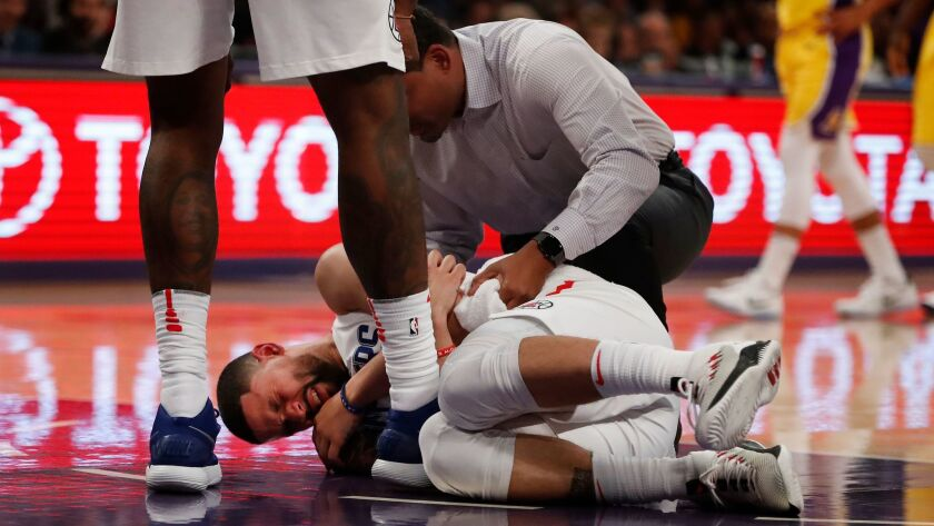 LOS ANGELES, CA - DECEMBER 29, 2017: A trainer tends to LA Clippers guard Austin Rivers (25) after