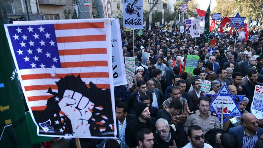 Holding anti-U.S. placards, Iranians attend a state-organized annual rally Nov. 3 in front of the former U.S. Embassy in Tehran.