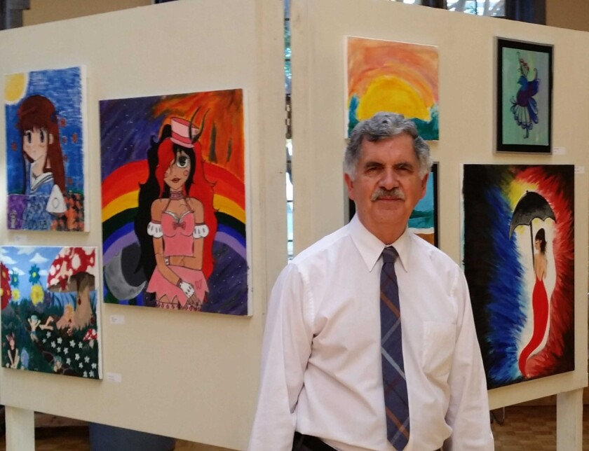 Curator Jay Belloli, in front of artwork.