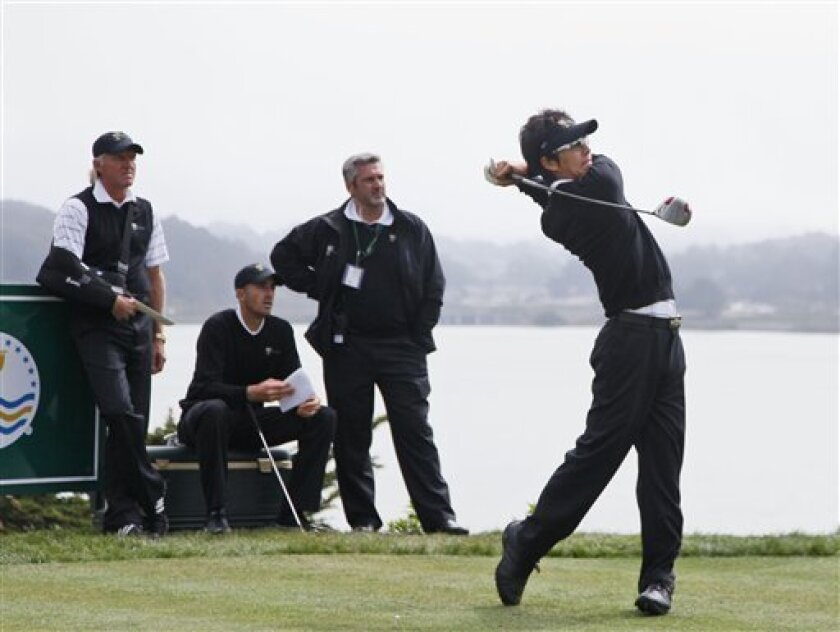 International captain Greg Norman, left, player Geoff Ogilvy, second from left, and captain's assistant Frank Nobilo watch Japan's Ryo Ishikawa hit his final tee shot during a practice round for the Presidents Cup golf matches Wednesday, Oct. 7, 2009, in San Francisco. (AP Photo/Eric Risberg)