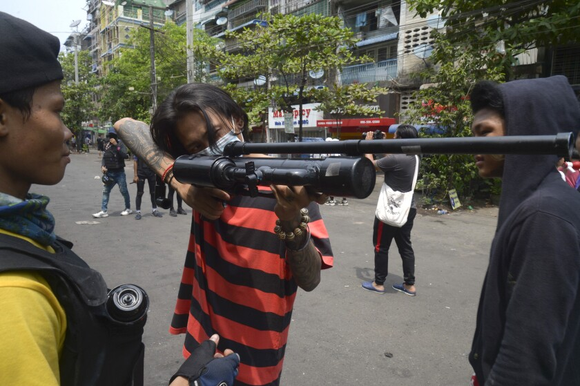 Anti-coup protesters aim with homemade air rifle during a protest in Yangon, Myanmar, Saturday, April 3, 2021. Threats of lethal violence and arrests of protesters have failed to suppress daily demonstrations across Myanmar demanding the military step down and reinstate the democratically elected government. (AP Photo)