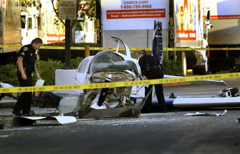 San Diego police examine the wreckage of a small plane as it rests in the parking lot of a Target store west of Montgomery Field Wednesday afternoon. Two women were transported to a hospital to be treated for their injuries, and officials report that one of the women aboard the plane has died.