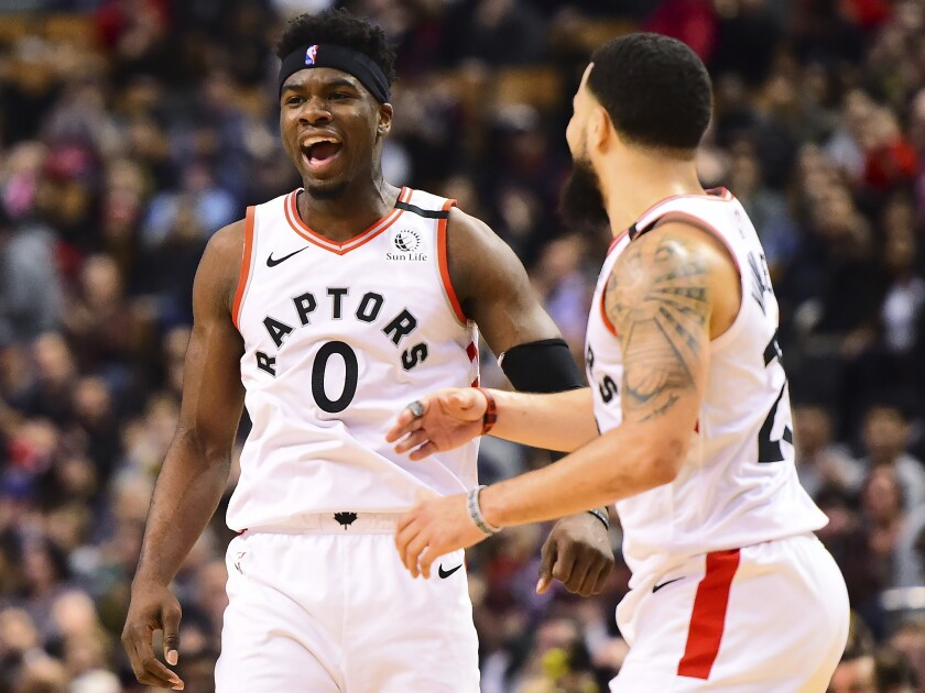 Toronto Raptors guard Terence Davis (0) and teammate Fred VanVleet (23) celebrate a basket during second-half NBA basketball game action against the Chicago Bulls in Toronto, Sunday, Feb. 2, 2020. (Frank Gunn/The Canadian Press via AP)