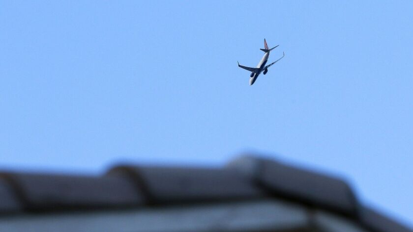 Just after sunrise, a passenger jet leaving Phoenix Sky Harbor International Airport flies low over
