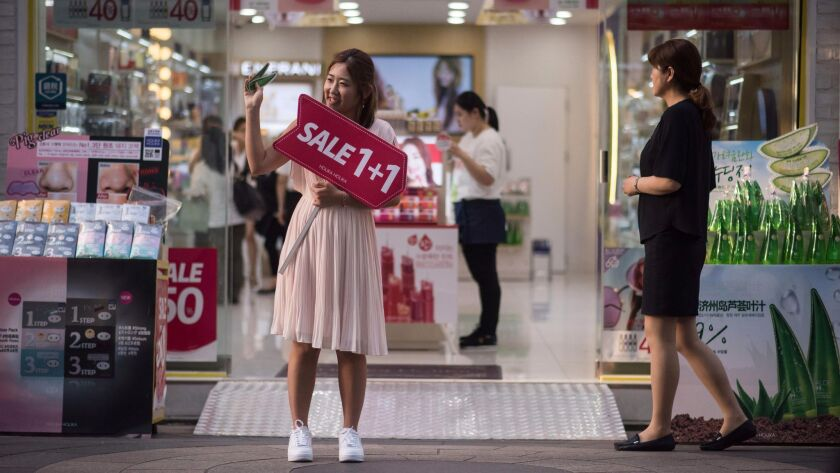 A salesperson advertises a sale in front of a cosmetics store in the popular Myeongdong shopping area of Seoul.