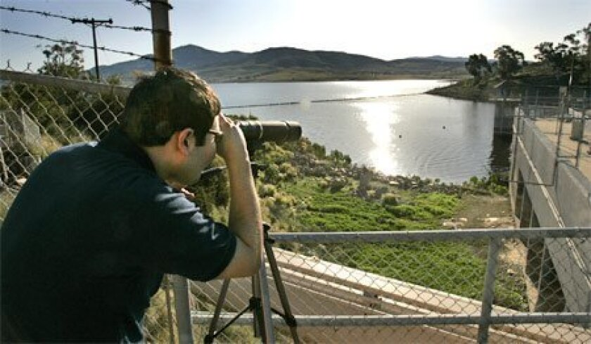 A Sweetwater Authority treatment plant operator checks the level of the Sweetwater Reservoir in Spring Valley in the file photo.