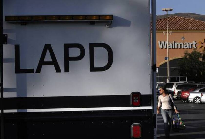 A woman walks past the LAPD's mobile command post in the parking lot at Wal-Mart in Porter Ranch. A series of violent incidents at recent Black Friday sales prompted beefed-up police deployment to control crowds of shoppers.