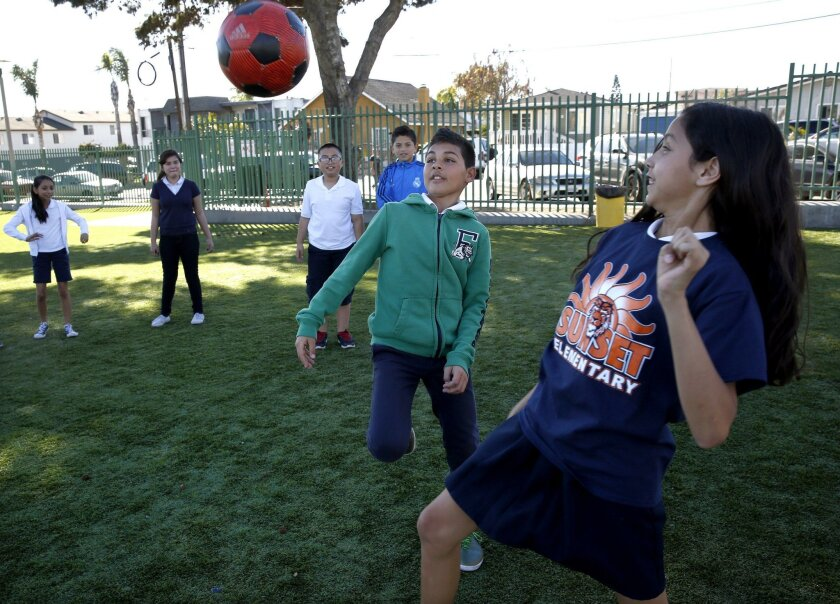 Students at Sunset Elementary School in the San Ysidro School District play soccer on a new, nearly $1 million artificial turf playground donated by Manzana Energy.