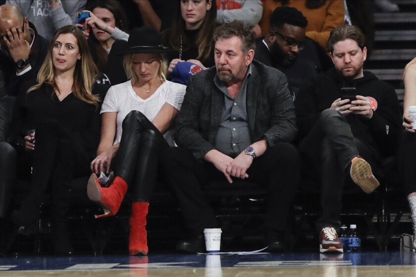 New York Knicks owner James Dolan, center, reacts with fans during the second half of the team's NBA basketball game against the Memphis Grizzlies on Wednesday, Jan. 29, 2020, in New York. The Grizzlies won 127-106. (AP Photo/Frank Franklin II)