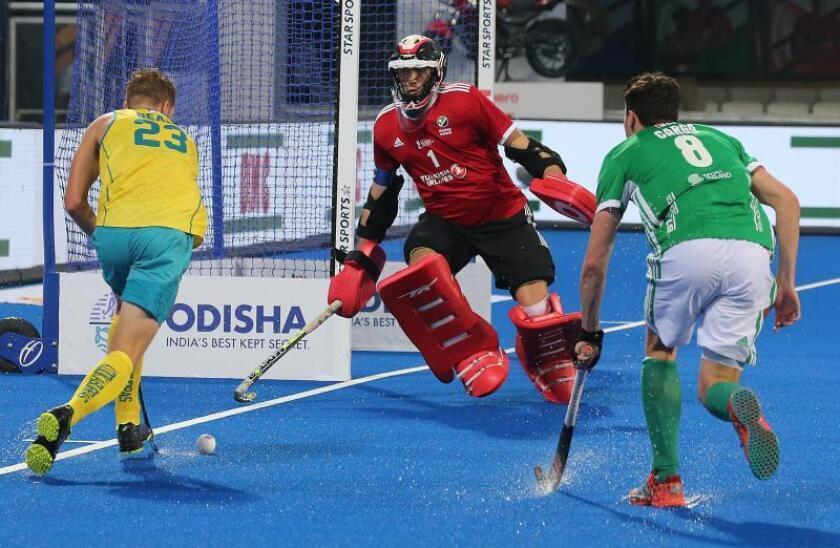El jugador de la selección australiana Daniel Beale (d) controla la bola ante el portero irlandés Chris Cargo (d) durante el partido del Mundial masculino de hockey hierba que disputaron ambos equipos en el Kalinga Stadium de Bhubaneswar, la India. EFE