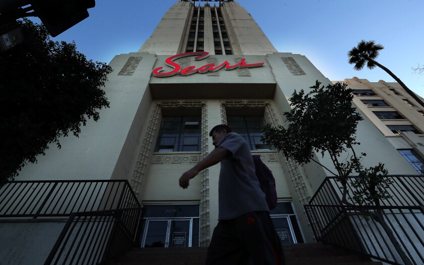 """A person walks an Art Deco tower with a neon """"Sears"""" sign."""