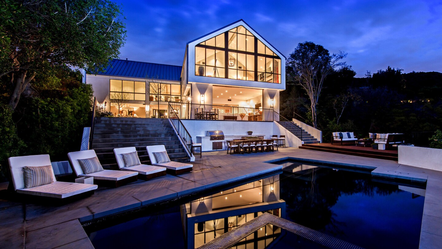 A two-year, multimillion-dollar renovation turned the dreary 6,000-square-foot Tudor into a warm, 9,393-square-foot contemporary farmhouse featuring clean, modern design, an open floor plan and extended panoramic views.