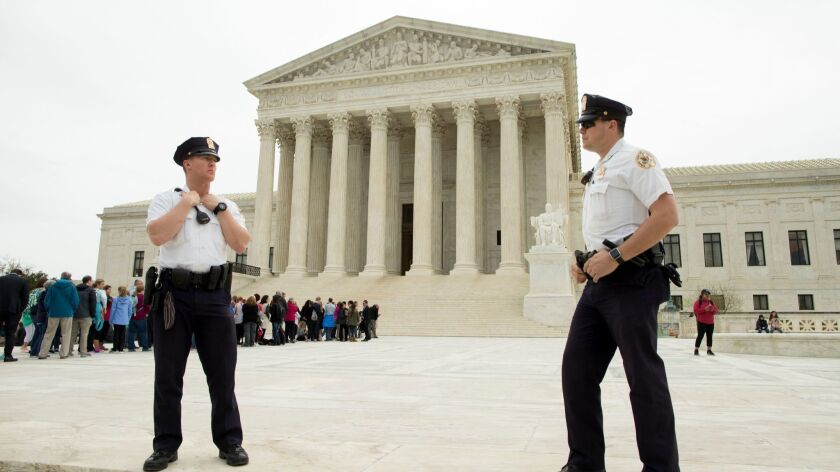 Police stand outside the Supreme Court, where justices on Tuesday denied terrorism victims' claims against Arab Bank, a Jordanian institution with offices in New York City that had been accused of facilitating the transfer of fund to terrorists.