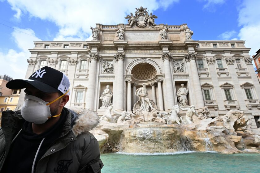 A masked tourist at Rome's Trevi Fountain