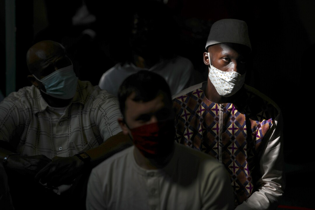 A man wearing a mask and hat sits next to other men, also masked