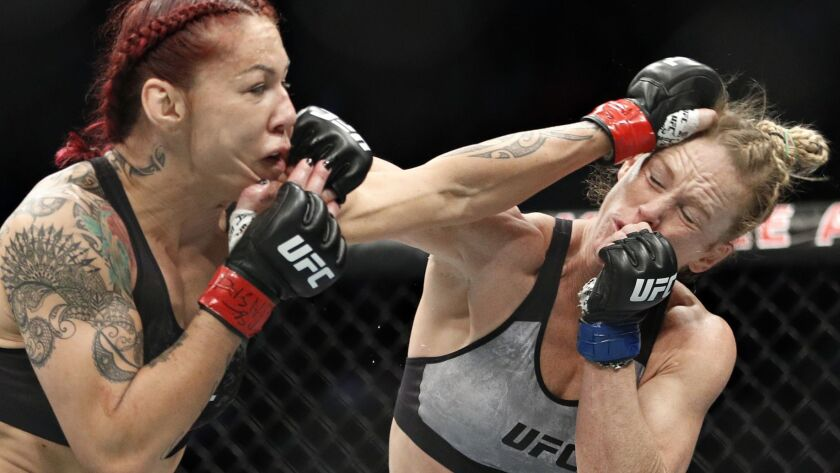Holly Holm, right, and Cris Cyborg exchange blows during a featherweight championship mixed martial