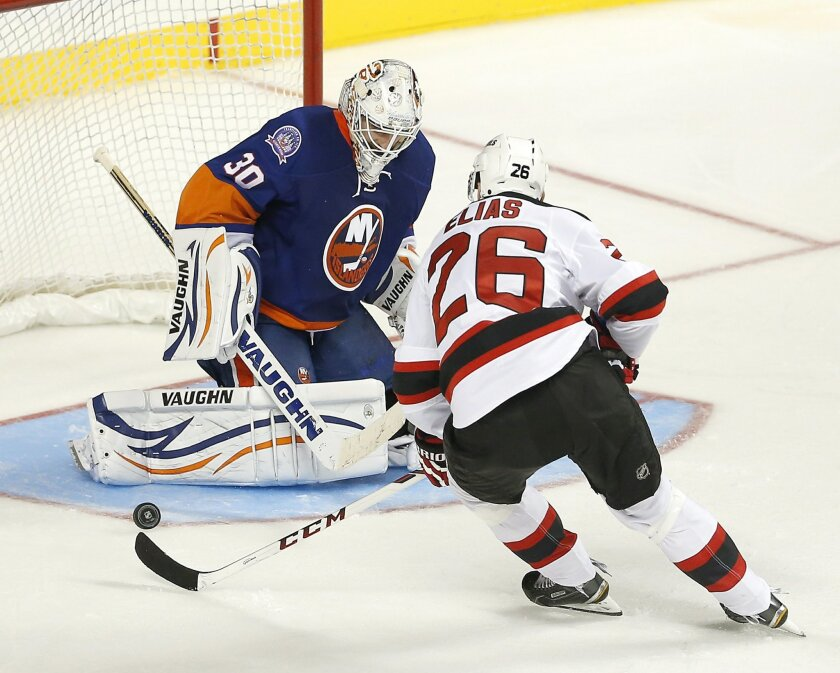 New York Islanders goalie Chad Johnson (30) stops a shot by New Jersey Devils left wing Patrik Elias (26) in the third period of a preseason NHL hockey game Friday, Sept. 26, 2014, in New York. The Islanders won 3-2 in a shootout. (AP Photo/Paul Bereswill)