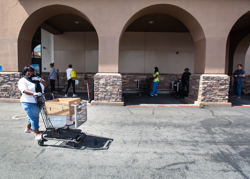 Shoppers are socially distanced in a line outside a Ralphs in Westchester on March 22.