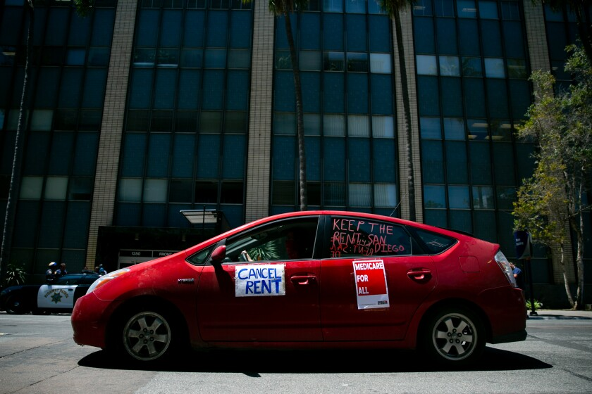 """Protesters in cars pass through downtown San Diego their cars as part of a """"Food Not Rent"""" caravan last year."""