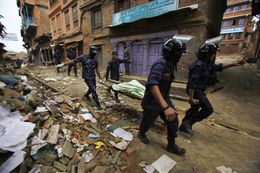 Nepalese rescue workers carry a body recovered from a collapsed building in Bhaktapur, near Katmandu.