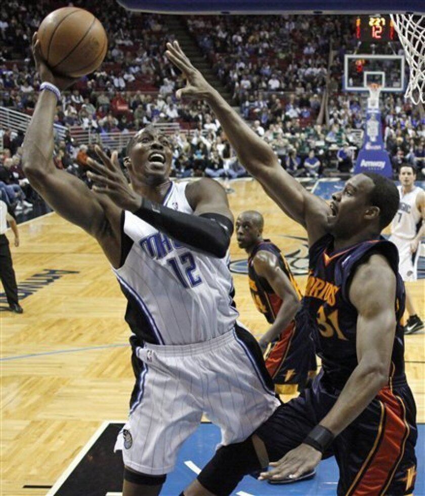 Orlando Magic center Dwight Howard (12) shots over Golden State Warriors forward Chris Hunter (31) during the first half of an NBA basketball game in Orlando, Fla., Wednesday, March 3, 2010. (AP Photo/John Raoux)