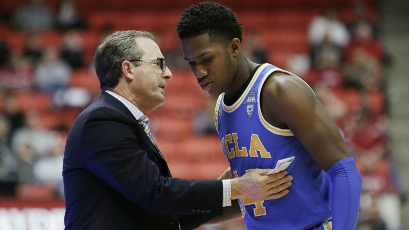 UCLA interim coach Murry Bartow, left, speaks with guard David Singleton during the second half of t