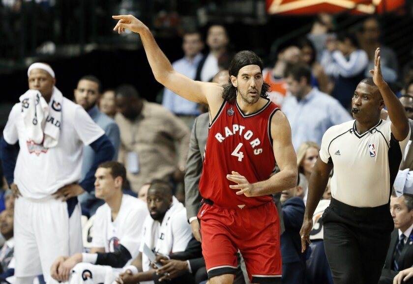 The Dallas Mavericks bench, left, looks on as Toronto Raptors' Luis Scola (4) of Argentina celebrates scoring a three-point basket late in the second half of an NBA basketball game Tuesday, Nov. 3, 2015, in Dallas. Scola had 19 points and 12 rebounds in the 102-91 Raptors win. (AP Photo/Tony Gutier
